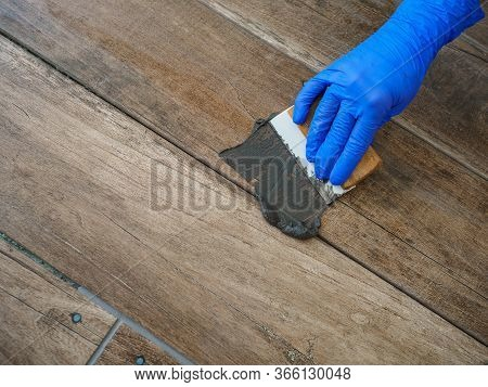 Grouting Between Ceramic Tiles. A Hand In A Blue Glove Holds A Spatula. Repair In The Room