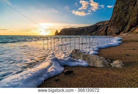 Bright Sea Sunset. The Waves Crash Into The Rock, Lit By The Warm Sunset, Sand And Pebbles, Volcanic