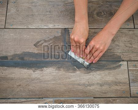Grouting Between Ceramic Tiles. The Girl Works With A Spatula. Repair In The Room.