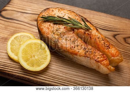 Grilled Salmon Steak With Lemon On Dark Background, Fried Salmon Fillet On Wooden Board, Close Up.