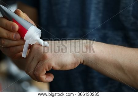 Close-up Of Person Applying Handcream From Plastic Tube On Hand. Moisturizing Sensitive Skin. Beauty
