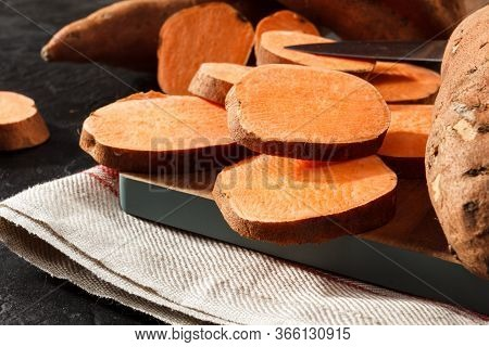 Organic Raw Sweet Potato Whole And Sliced On Wooden Kitchen Board. Rustic Style.