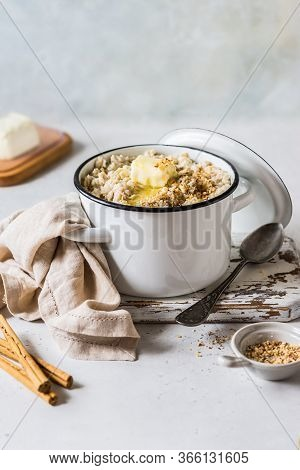 Cinnamon Old Fashioned Rolled Oat Porridge With Melting Butter In A Sauce Pan Topped With Chopped Al