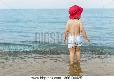 Cute Adorable Little Blond Caucasian Serious Pensive Toddler Boy In Red Panama Walking Through Blue