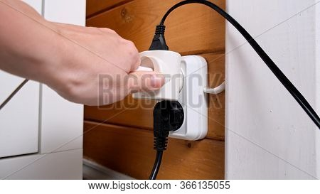 A Hand Pluging A Socket Into The Outlet, Overloaded Outlet With An Extension And Many Sockets Plugge