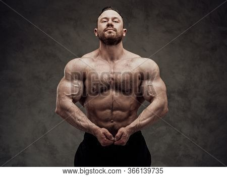 Sportive Adult Male Wearing Sportswear Posing, Showing His Chest Muscles And Looking At The Camera I