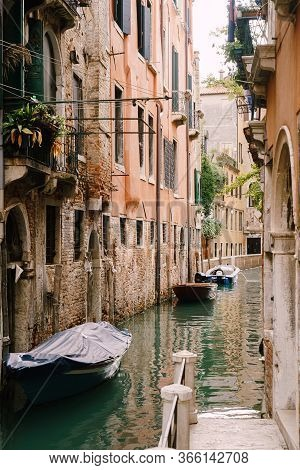 Boats Moored At The Walls Of A Building In A Canal In Venice, Italy. Classic Venetian Street Views -