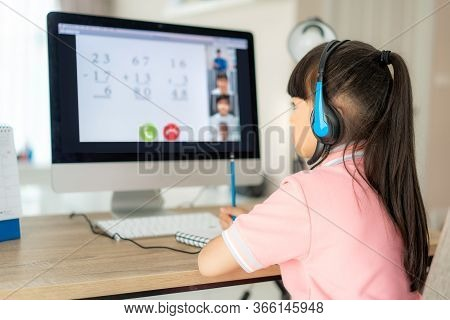 Asian Girl Student Video Conference E-learning With Teacher And Classmates On Computer In Living Roo