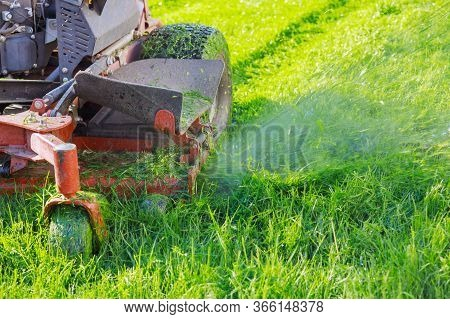 Man Using A Lawn Mower A Gardener Cutting Grass By Lawn Mower