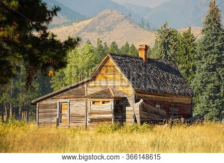 An Abandoned Wooden Cabin Sits Quietly In An Autumn Meadow With Mountains In The Background.