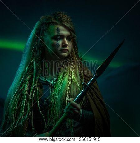 Female viking warrior against Aurora Borealis