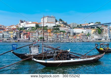 PORTO, PORTUGAL - AUGUST 29, 2018: A view of some moored boats in the Doure River, with the Ribeira district of Porto, in Portugal, in the background and the famous Dom Luis I Bridge on the right