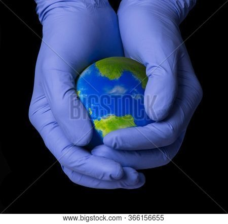 Doctor hand hold and protect planet earth with surgery gloves.