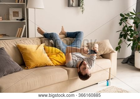 Young bearded man sitting upside down on sofa in living room and playing online game on smartphone in self-isolation
