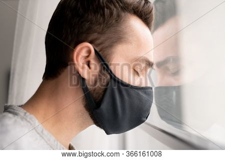 Sad puzzled young man in cloth mask leaning head on window and keeping eyes closed while feeling depression because of coronavirus isolation