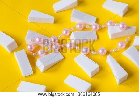 Lots Of White Triangular Sponges And Pink Pearl Beads On A Yellow Background