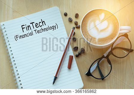 Concept Fintech Message On Notebook With Glasses, Pencil And Coffee Cup On Wooden Table.