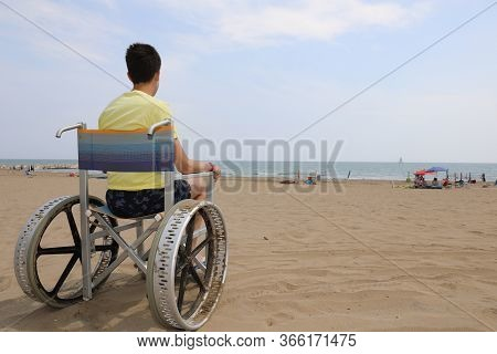 Boy In A Special Wheelchair With Very Big Metal Wheels To Move On The Beach By The Sea In Summer