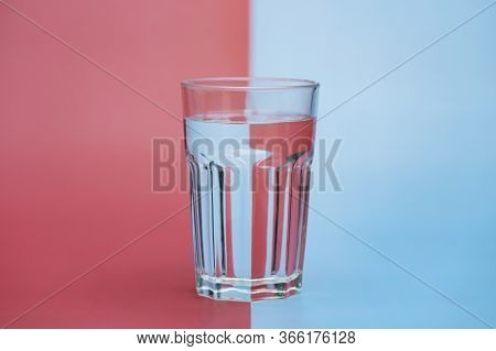 Transparent Glass Of Water, Clean Drinking Water In A Clear Glass  On Two Tone (pink And Blue) Backg