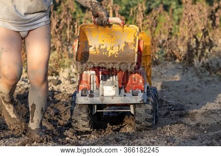 A Child Drives A Large Dump Truck On Dirty Soil. Feet, Children's Hands And A Dump Truck In The Mud.