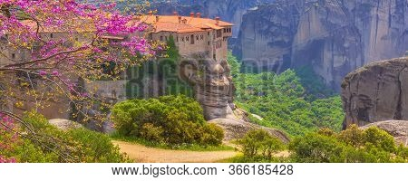 Orthodox Varlaam Monastery In Meteora, Greece On High Mountain Rock And Pink Cherry Tree Flower Blos