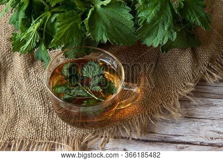 Herbal Tea From Nettle Dioecious In A Glass Cup Close-up On Burlap On A Wooden Background. Alternati