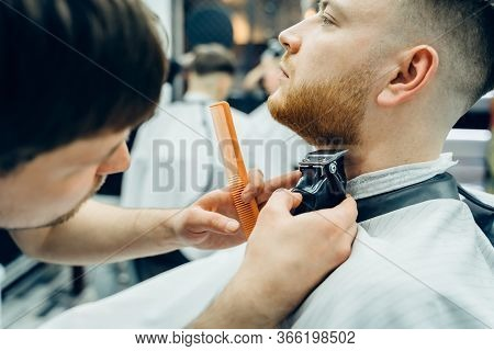 Barber Trimming Bearded Man With Shaving Machine In Barbershop. Hairstyling Process. Close-up Of A H