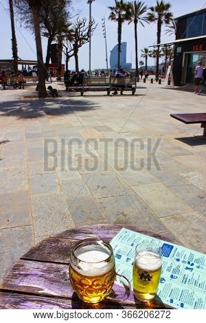 Barcelona, Catalonia, Spain - April 15, 2015: a view of Barceloneta Beach, the most popular beach in Barcelona. W Barcelona Hotel (Hotel Vela) seen in the distance, beer in front.