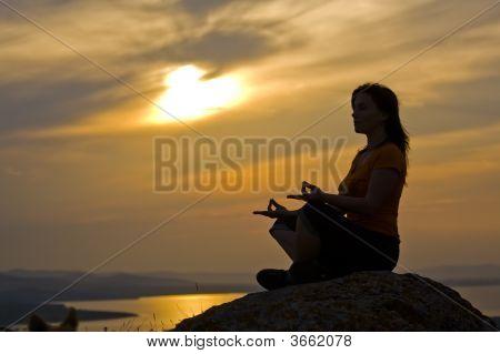 Woman Meditating At The Sunset