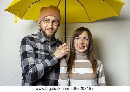 Young Couple, A Man With A Beard In A Hat And A Plaid Shirt And A Girl In A Sweater Are Smiling Unde