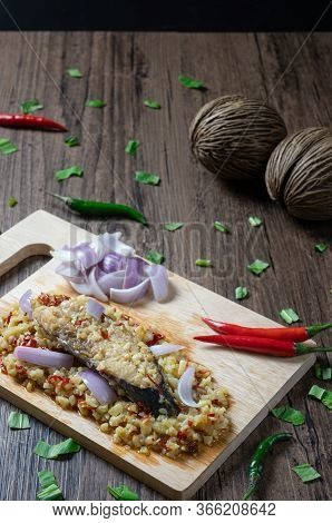 Steam Salted King Mackerel Fish With Minced Garlic And Chili Salad On Wooden Background. ( Spicy Tha
