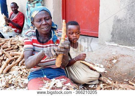 16 July 2019 - Kisumu, Rwanda : A Woman Peeling A Cassava Root In Northern Rwanda.