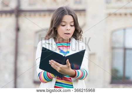 Developing Her Reading Skills. Little Girl Read Book Outdoor. Small Kid Enjoy Reading Day. Adorable