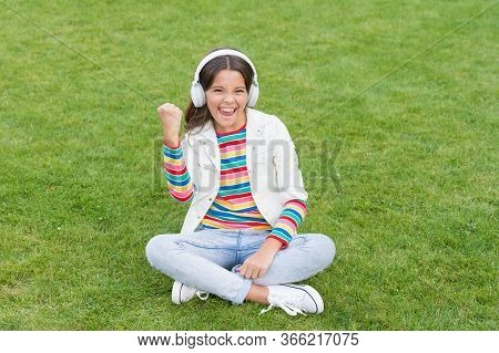 Happiness Is Not Something You Sit Back And Wait. Listen Music While Relaxing Outdoor. Kid Girl Enjo