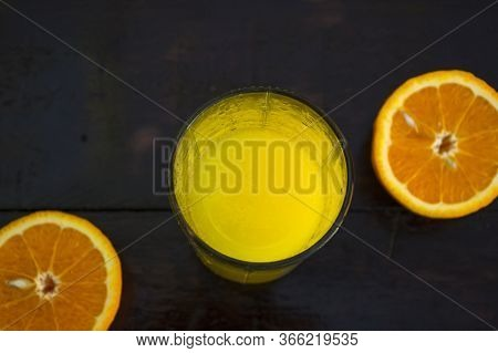 Orange Juice In A Glass On A Wooden Background. Orange Cut In Half, Lies On The Table.