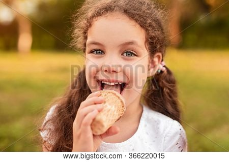 Delighted Little Girl With Curly Hair Licking Sweet Ice Cream And Looking At Camera While Resting In