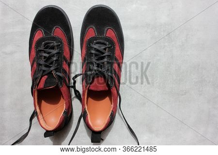 Pair Of Orthopedic Sports Shoes On A Gray Concrete Background With Copy Space. Close-up Of Suede Bur