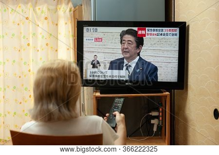 Fuji City, Shizuoka, Japan - May 14, 2020: Coronavirus (covid-19) Pandemic. A Woman Watches On Japan