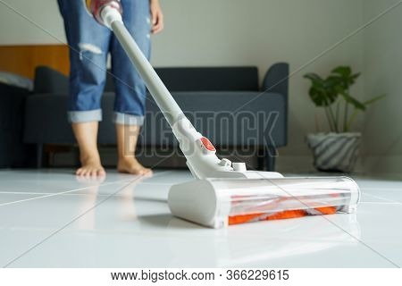 Maid Cleaning The House, Mop The Floor, Vacuum Using A Handheld Vacuum Cleaner. Eliminate Germs And