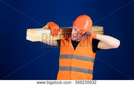 Carpenter, Woodworker, Labourer, Builder On Tired Face Carries Wooden Beam On Shoulder. Man In Helme