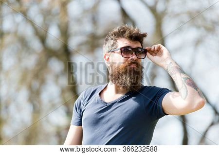 Man With Beard And Mustache Wears Sunglasses On Sunny Day, Defocused Background. Hipster On Confiden