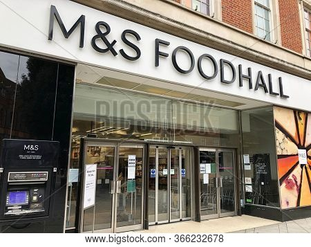 READING, UK - MAY 3, 2020: Notices in the windows of M&S Foodhall highlight shopping restrictions during the Coronavirus pandemic in Reading, Berkshire, UK.