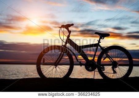 Black Silhouette Of A Bicycle At Sunset On The Beach Near The Lake.