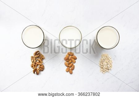 Almond, Walnut, Oat Milk On Marble Background Top View. Nut Milk Vegan Lactose-free, Dairy Free Milk