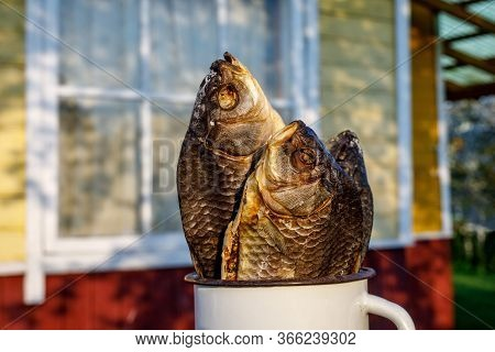 Dried Fish In A White Mug With A Country House Background.