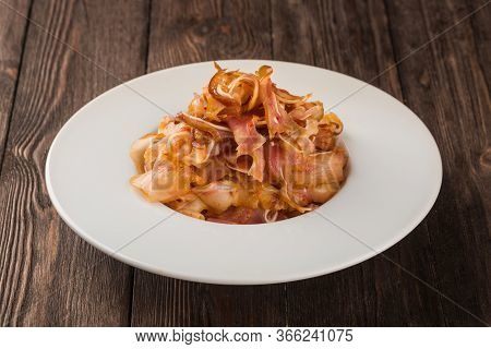 Grilled Pork Ears. In A White Plate On A Wooden Background.
