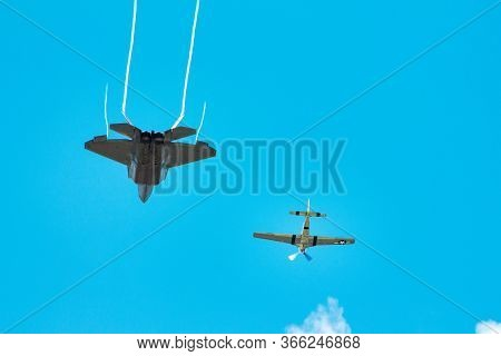 Two Jets Flying In The Air Close To Each Other At An Airshow