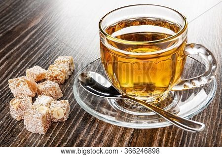 Pieces Of Rahat-lokum, Transparent Cup With Tea, Teaspoon On Saucer On Dark Wooden Table