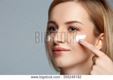 Close up smiling woman apply cream or lotion on face with finger. Skin care, sunscreen, moisturizing and nourishing. Beauty cosmetic industry
