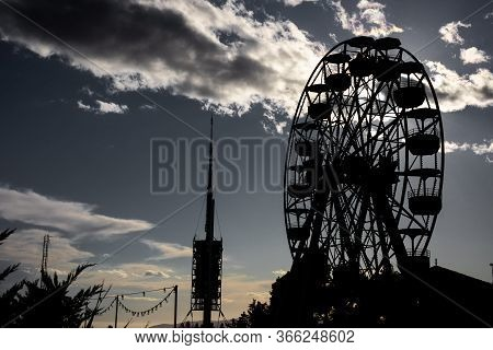Fair Ferris Wheel And Telecommunications Antenna Silhouettes On Cloudy Day With The Sun Rays Passing